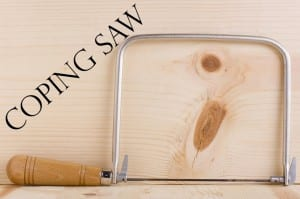 Coping saw next to a piece of wood.