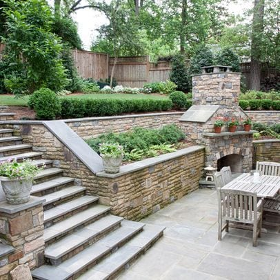 a rock wall doubles as a planter for slope yard landscaping ideas