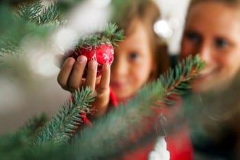 Familie schmückt Weihnachtsbaum
