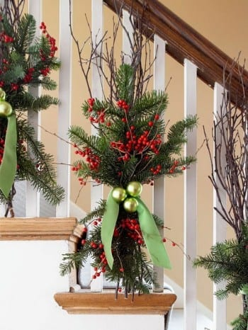Decorate Your Staircase For Christmas by BHG - Instead of swags of greenery trailing down the banister, try these greenery bunches. Natural birch branches form the backbone, but red twig dogwood or other branches would work just as well. Use thin florist's wire to lash them to the banister posts along with evergreens and sprays of bright red winterberries. Matte and glossy chartreuse ornaments add pops of color. Tie it all together with a chartreuse velvet ribbon.