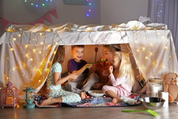 A fort with kids inside. Fort was built using a table, sheets, and lights