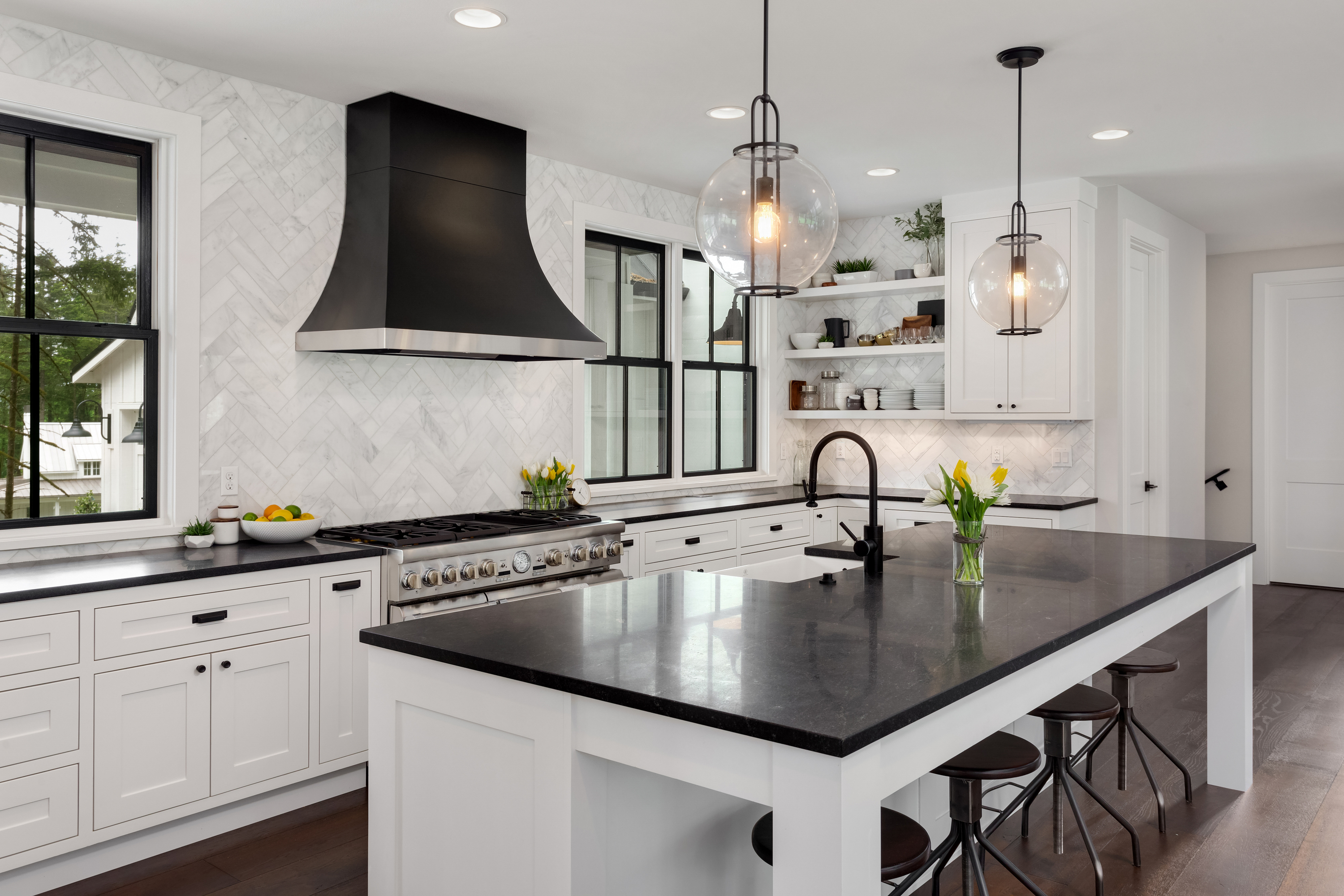 Isn't this kitchen gorgeous! The contrasting look of white cabinets black granite really just pops. If you're for more black and white kitchen ideas, look here.