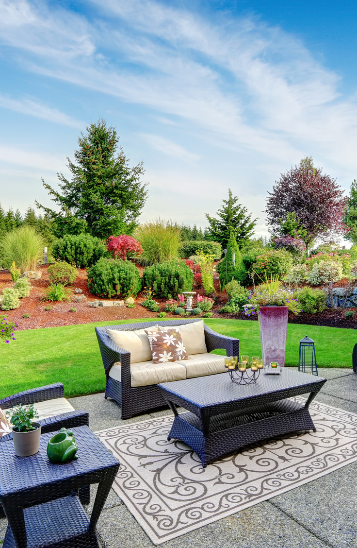 Backyard Projects: Landscape Sloped yard with shrubs and flowers and patio seating